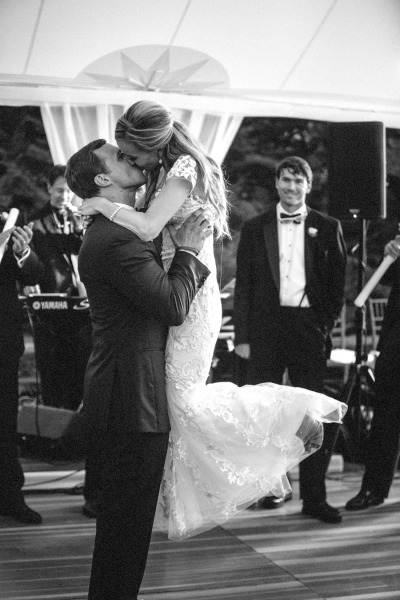 groom picks up bride during first dance and kisses her