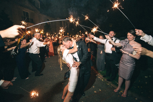 bride and groom kiss in brides party dress under sparklers