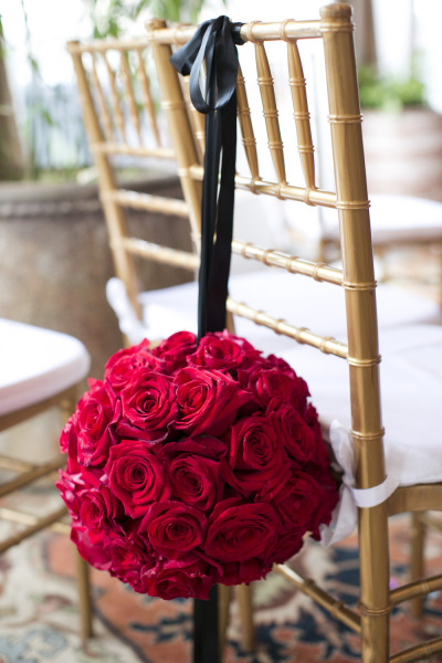 ball of red roses on back of wedding ceremony chairs