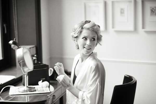 bride putting on makeup with hair in curls
