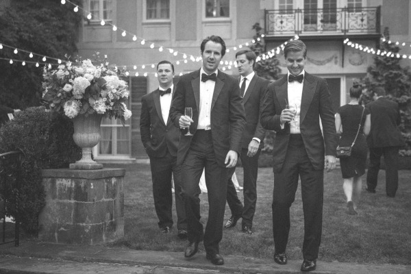 groomsmen in black tuxedos outside with a large bouquet and hanging edision lights