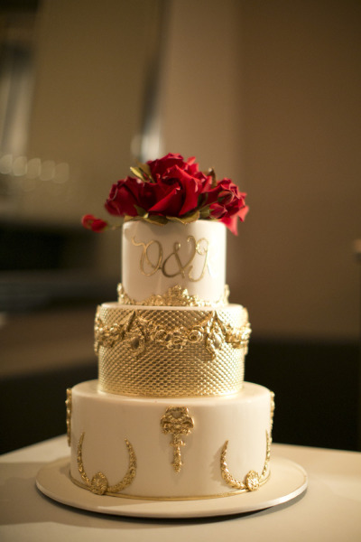 white and gold wedding cake with red roses