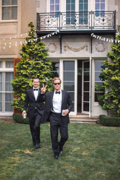 groomsmen in black tuxedo doing a pea<br /><br /> ce sign