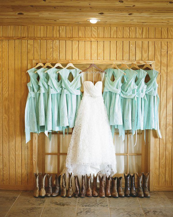 wedding dress hanging next to mint dresses with keyhole back and cowboy boot beneath