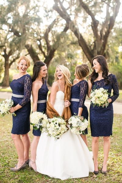 bride laughing with bridesmaids in navy lace one shoulder dresses