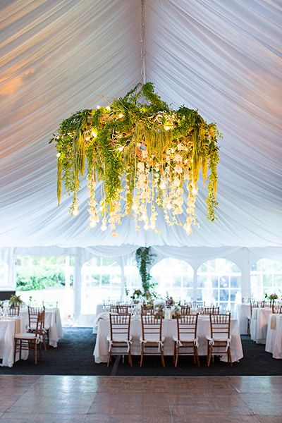 white marquee tent with large hanging greenery and orchid arrangement