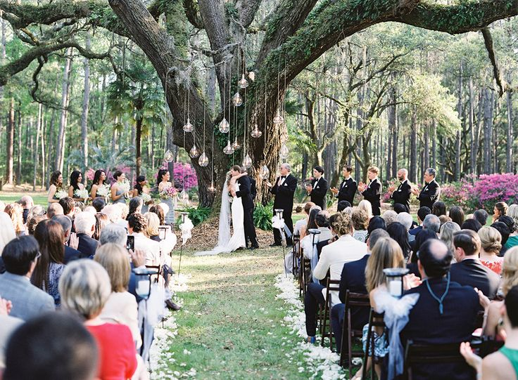 outdoor ceremony under large oak tree with hanging lights