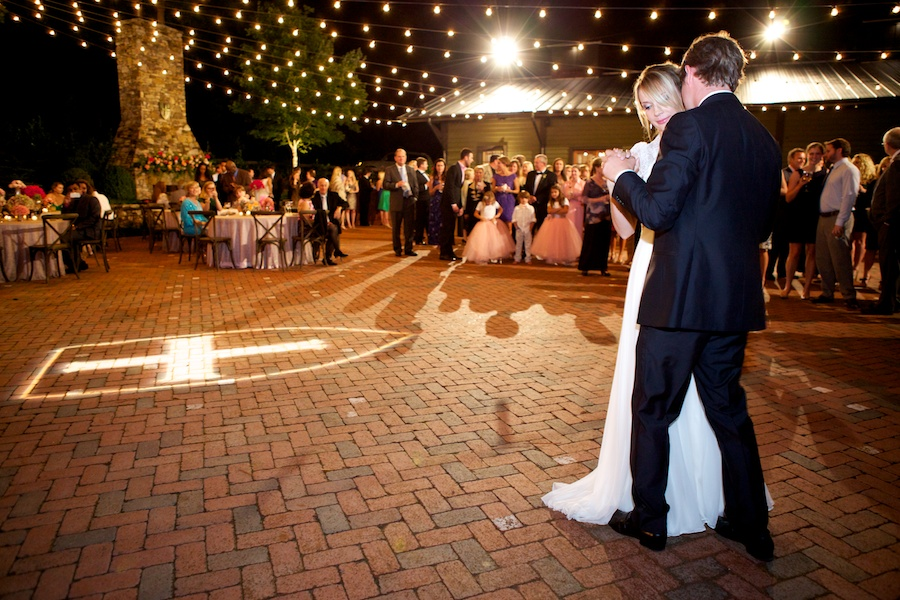bride and groom dancing outdoors under edison lights and guests watching