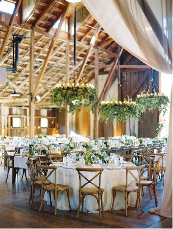 white and greenery wedding reception room with hanging greenery