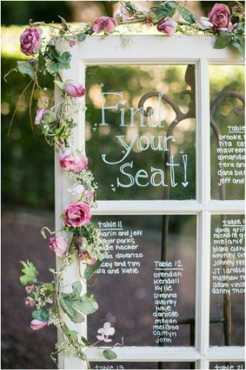 wedding seating chart written on white vintage window
