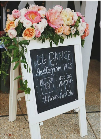 white framed chalkboard sign with wedding message about which hashtag to use for their wedding decorated with pink and white florals