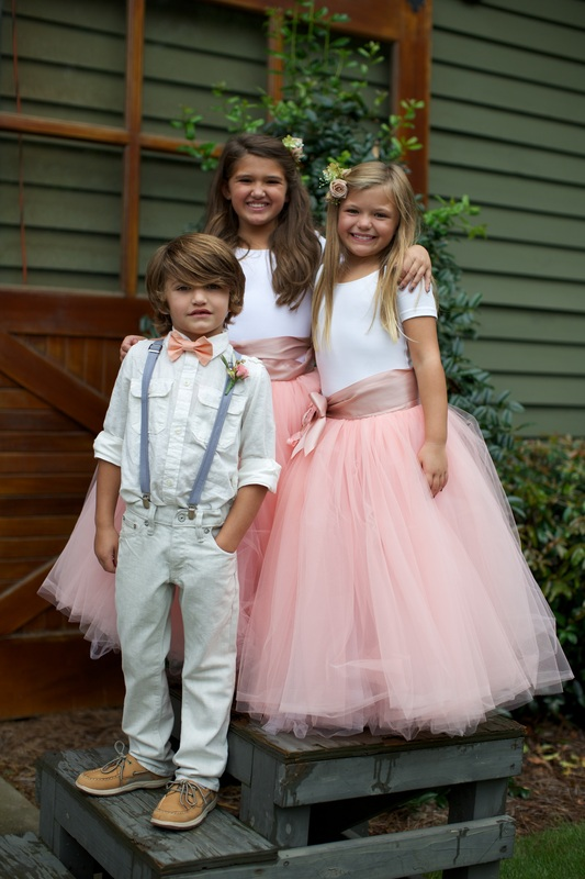flower girls in pink tulle skirts and ring barrier in suspenders