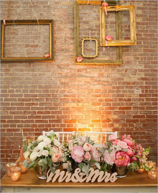 hanging gold frames as decor behind Mr and Mrs sign and floral arrangement