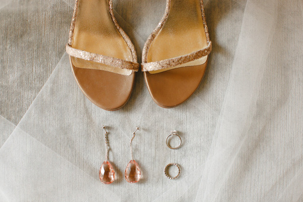 wedding shoes next to wedding rings and pink earrings