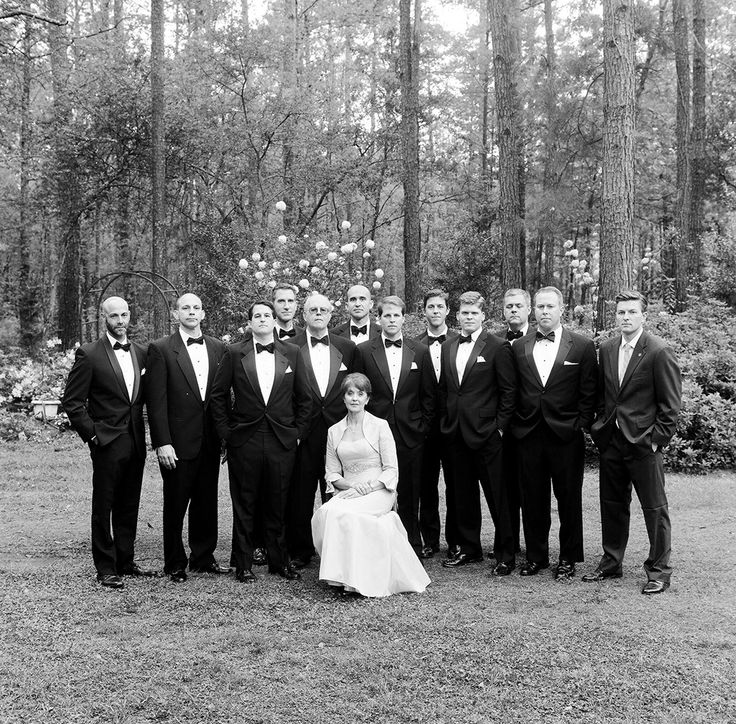 men in black-tie standing and mother sitting in white dress