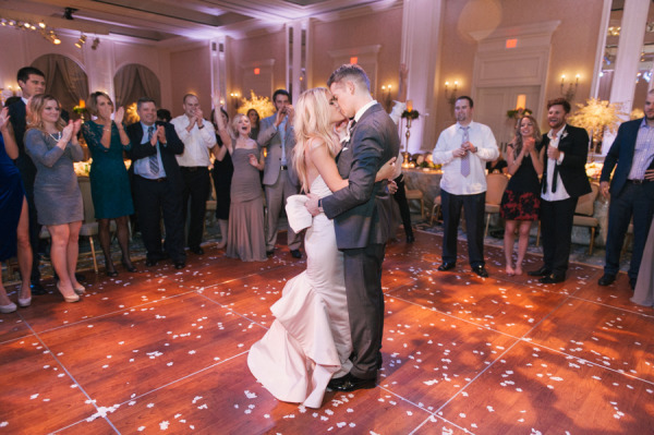 bride and groom kiss on the dance floor with confetti on the floor