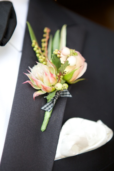 boutonniere with plaid tie on grooms black jacket