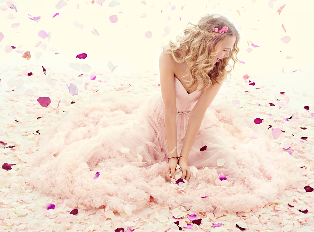 Girl in light pink strapless wedding dress with beaded belt and rose petals flying all around