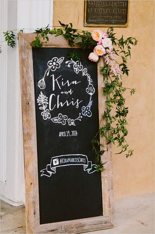 floor chalkboard with wedding date, and # the couple's last name with peonies in the corner, wedding hashtag