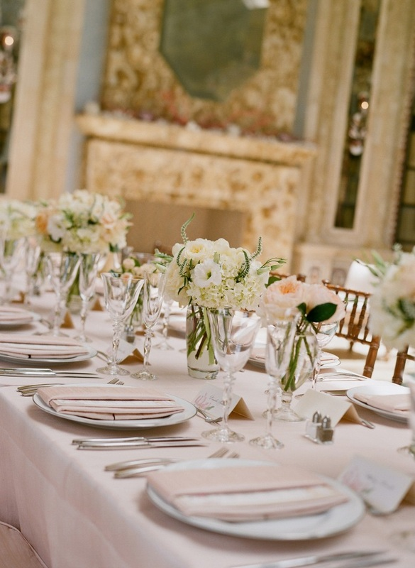 light pink table linens and white and peach bouquets