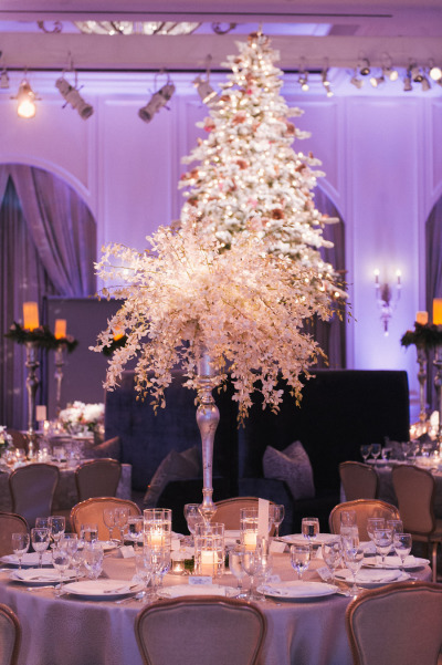 tall white orchid arrangement at wedding reception table with white christmas tree in the background