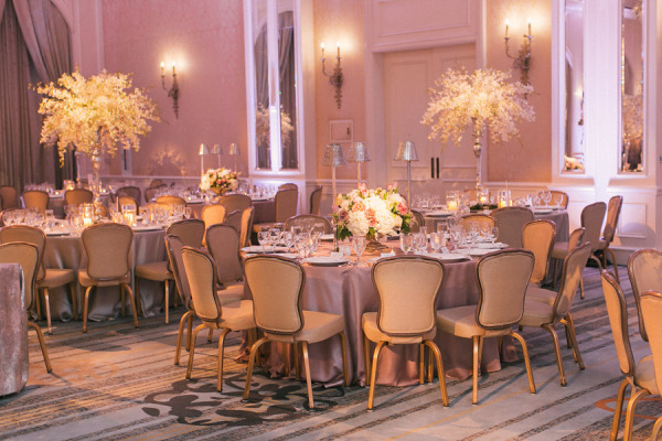 round wedding reception tables with silver linens, purple uplights and different flower centerpieces