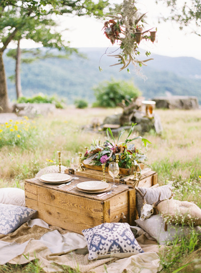 outdoor picnic with rustic flowers, candle sticks and pillows