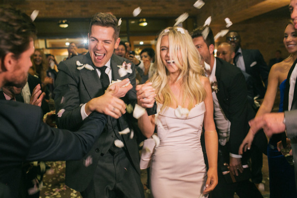 bride and groom exit with guests tossing white rose petals