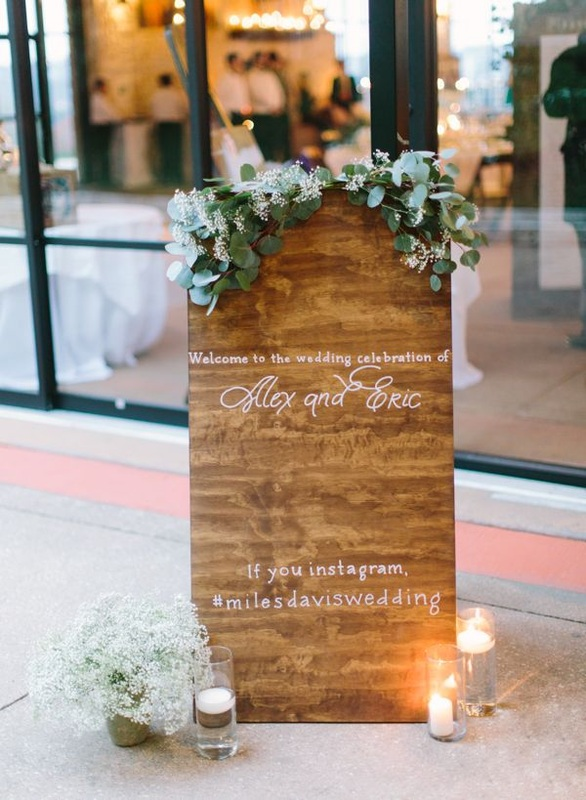 floor sign with pretty green leaves and baby's breath of the couples wedding hashtag name