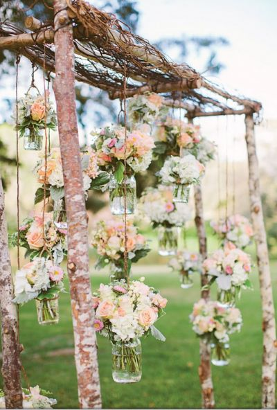 branch arbor with hanging mason jars filled with white and peach florals