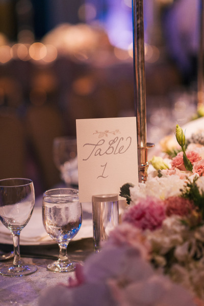 table numbers next to white and pink flowers
