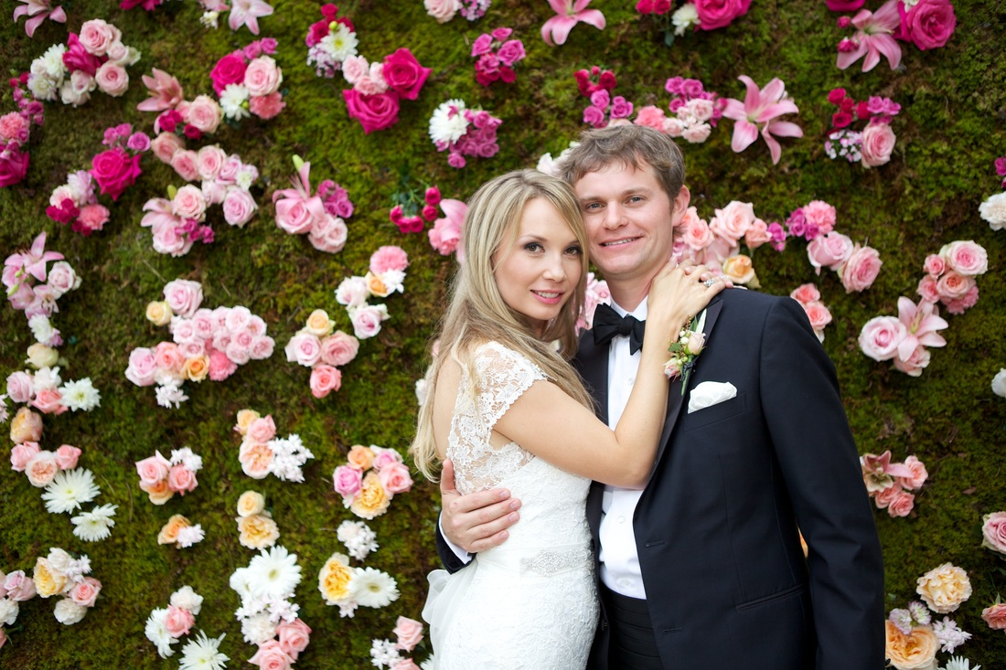 bride and groom standing next to hedge wall covered with roses