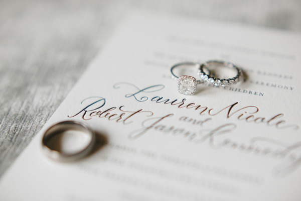 wedding rings on top of wedding invitations