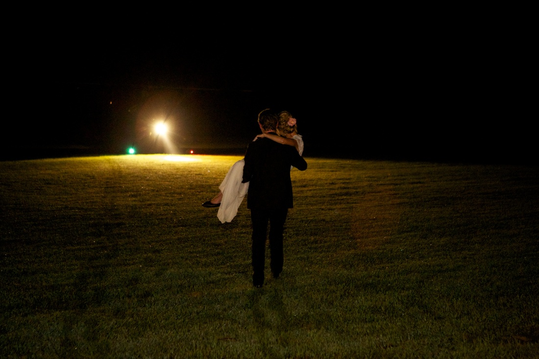 groom carrying bride over grass after wedding reception
