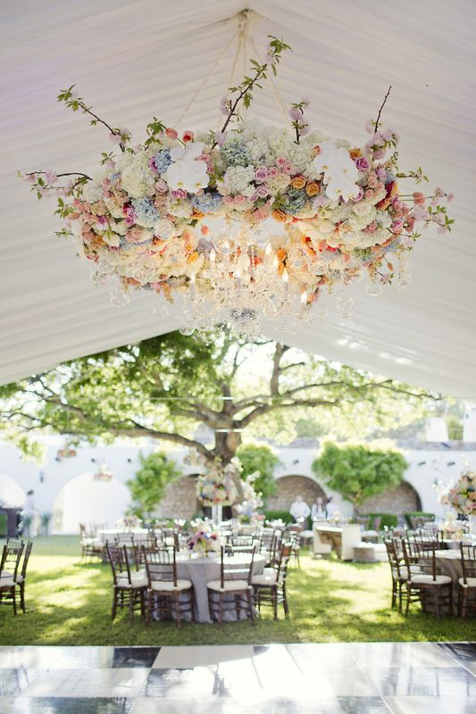 white marque tent with over-the-top hanging floral arrangement and white chandelier