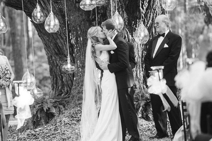 bride and groom kiss under large oak tree with hanging lights
