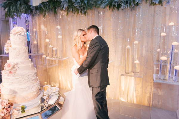 bride and groom kissing while cutting the cake against a glitter backdrop with candles