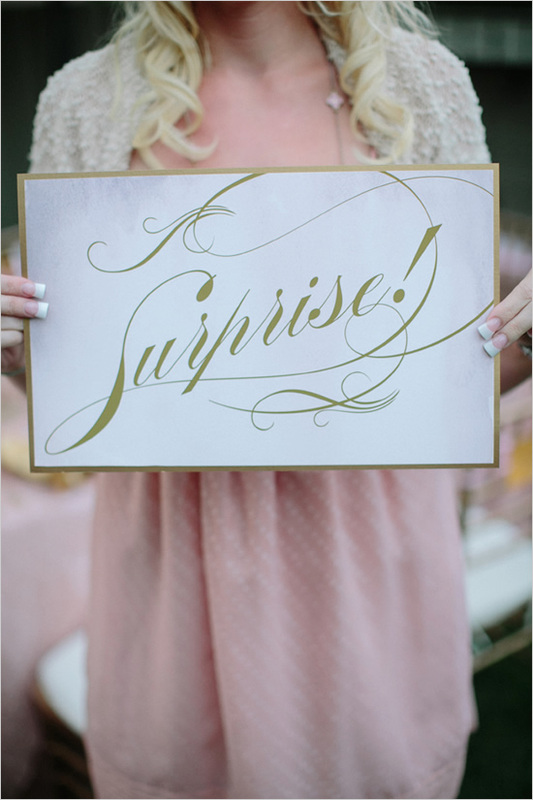 girl holding a white sign that says surprise in gold writing