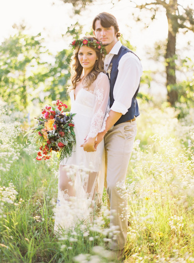 couple standing in a field, girl in sheer wite lace dress and flower halo