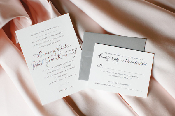 wedding invitations on top of blush pink wedding dress