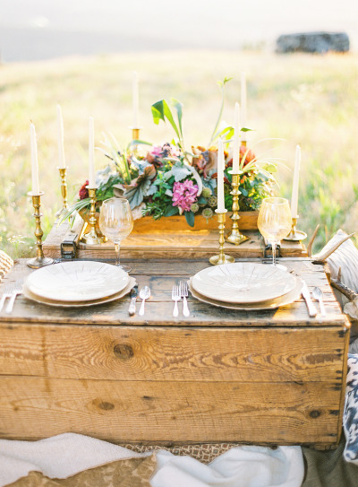 wood table with flowers, candlesticks and place settings in a open field