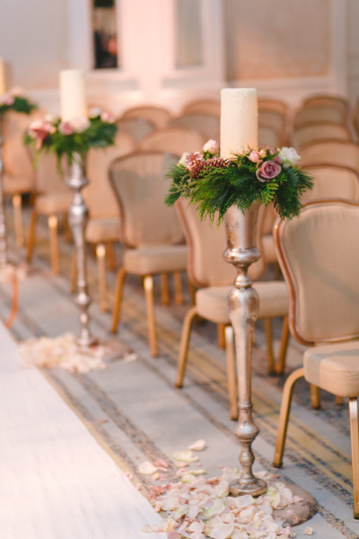 wedding aisle with evergreen, candles and petals