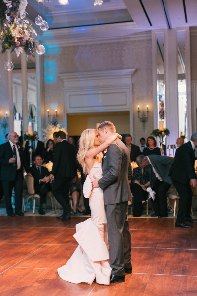 bride and groom kissing during first dance, bride in blush pink wedding dress