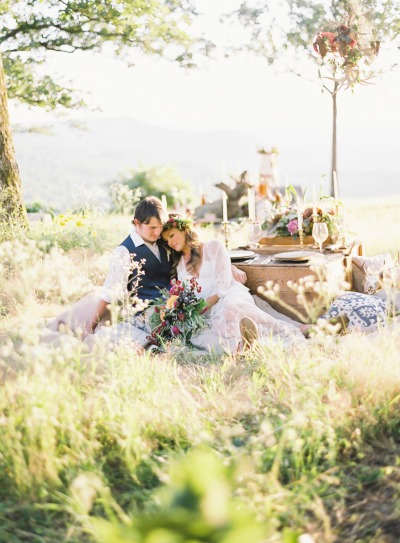 couple outside next to rustic table setting