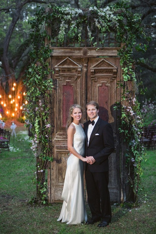 Cameran Eubanks and Dr. Jason Wimberly in front of rustic doors decorated with greenery