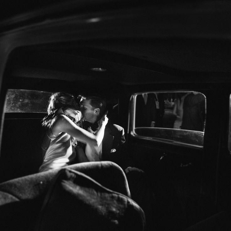 bride and groom kiss in the back of a limo after their send off