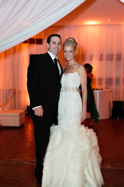 bride in lazaro lace dress with layers of tulle at the bottom and a beaded belt, groom in black tux with warm uplights in the backdrop