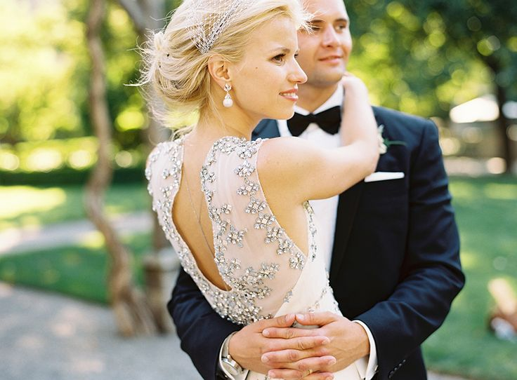 groom holding bride, wedding dress embellished with crystals and back necklace