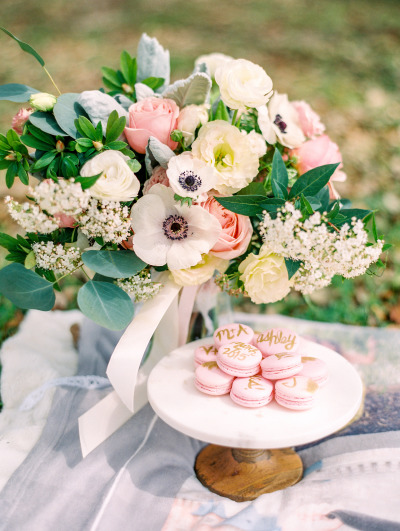 pink macaroons on cake stand with large bouquet of roses and baby's breath on picnic blanket
