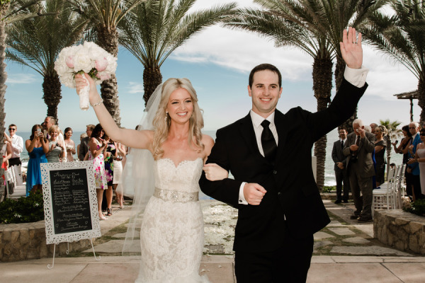 bride and groom holding arms out celebrating after wedding ceremony with ocean and palm trees in the backdrop